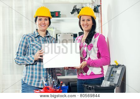 Craftswoman holding a white board in the workshop