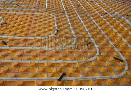 Orange posed Underfloor heating tube in a construction site poster