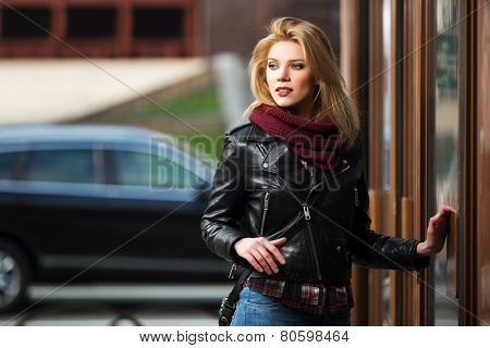 Young fashion blond woman in leather jacket at the mall door