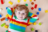 Little blond child playing with lots of colorful plastic blocks indoor. Kid boy wearing colorful shirt and having fun with building and creating. poster