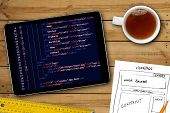 website wireframe sketch and programming code on digital tablet screen poster