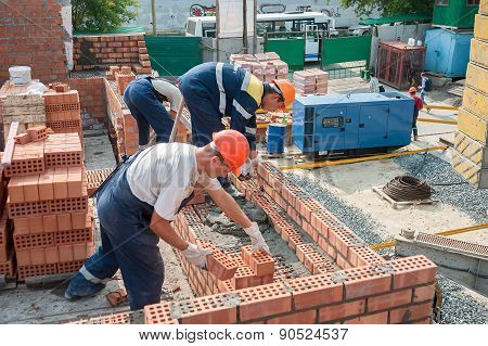 Team of bricklayers on house construction