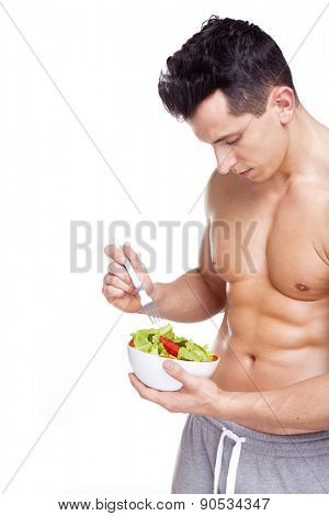 Young fitness man holding a bowl of salad, isolated on white background