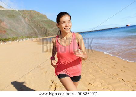 Running sports athlete runner woman on beach sweating and jogging. Fit exercising female fitness model working out training for marathon run. Biracial Asian Caucasian sports girl.