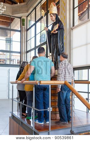 S. Bento da Porta Aberta, Portugal. April 06, 2015: Pilgrims worshiping St Benedict statue in the Crypt. Pope Francis raised the sanctuary church to Basilica in the 400th anniversary, March 21st
