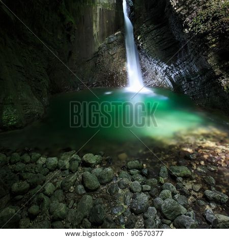 Romantic Waterfall Flowing Through A Crevasse To Green Lake