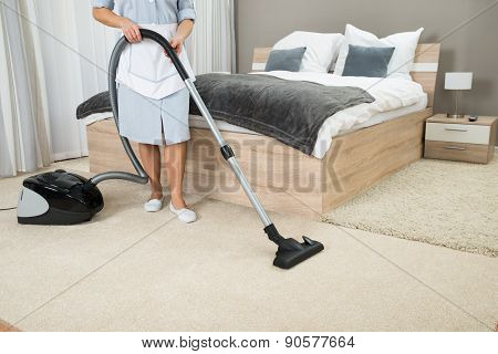 Female Housekeeper Cleaning With Vacuum Cleaner