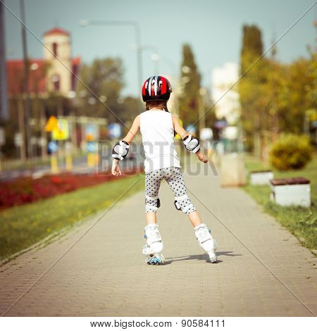 little cute happy girl rollerblading through the city streets. back view
