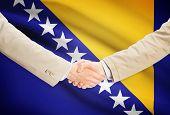 Businessmen shaking hands with flag on background - Bosnia and Herzegovina poster