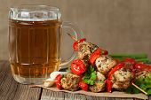 Gourmet chiken kebab skewer barbecue meat on bamboo sticks with glass of beer on rustic wooden table background. Rustic style, natural light. poster