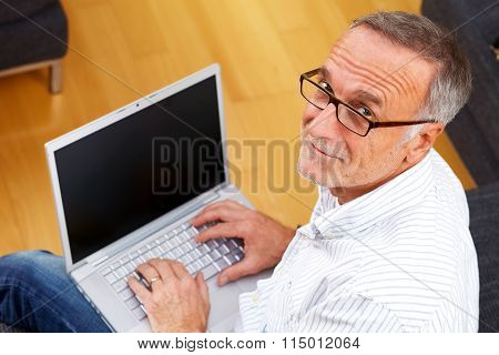 Mature Man With Laptop And Reading Specs