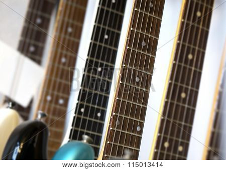 Electric guitars aligned on a stand or instrument store show case. Shallow depth of field.