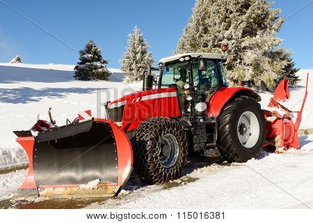 Large Red Tractor With Snow Plow  During A Winter