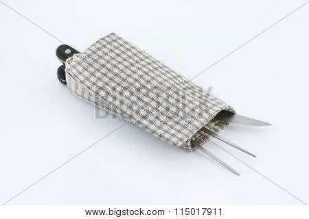 carving set wrapped in checkered dishtowel