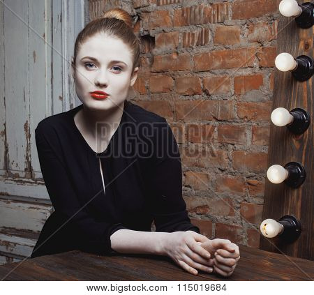 young stylish woman in make up room with mirror, diva actress before perfomance thinking art