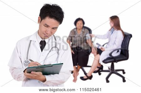 Doctor Writting Medical Report With Female Doctor Measuring Blood Pressure Of Senior Woman