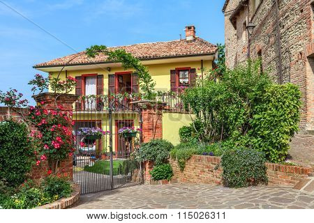 Brick fence with metal gate in front of small yard and typical italian house in Piedmont, Northern Italy.