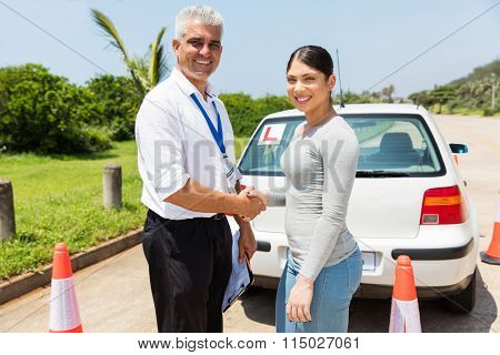 senior driving instructor and learner driver handshaking in testing ground
