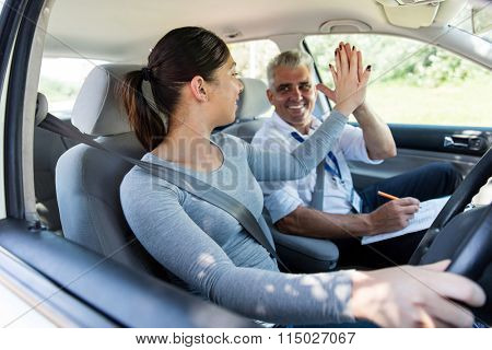cheerful young learner driver and driving instructor high five