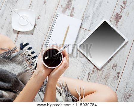 Woman with a cup of coffee, notepad and tablet at home. Freelancer