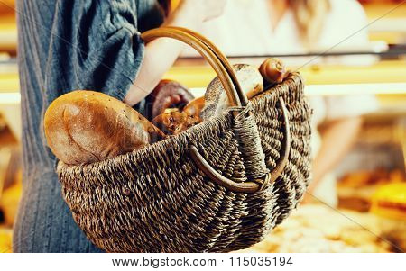 Customer shopping bread in baker carrying basket, filtered image