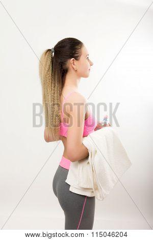 Young athletic girl finished training, holding bath towel