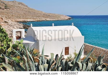 A small seafront chapel by Pondamos beach at Emborio on the Greek island of Halki.