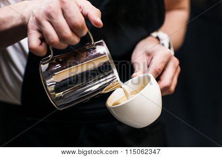 Barista making coffee pouring milk