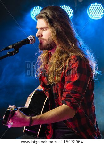 Playing Acoustic Guitar And Singing On Stage
