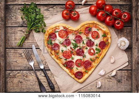 Heart shaped pizza for Valentines day with pepperoni, mozzarella, tomatoes, parsley and garlic on vi