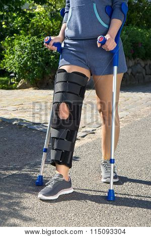 Woman Wearing A Leg Brace Walking On Crutches