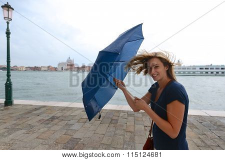 Woman Fights Wind With Umbrella In Venice, Italy