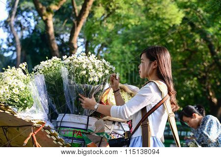 Young girl buy daisy flower from vendor in a street in Hanoi