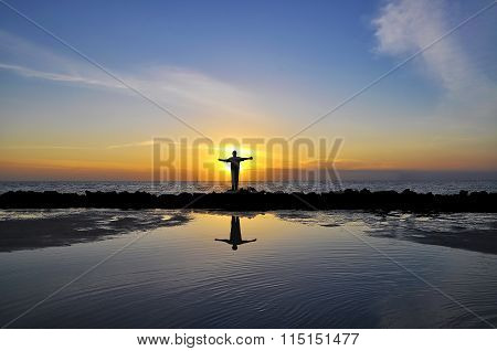 Reflection Of Man Open Arms Facing Sun Standing On Wave Barrier Rock At Straits Of Malacca