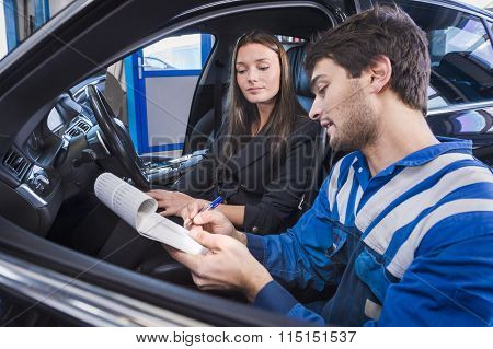 Car expert shows the checklist of repaired items to customer in garage