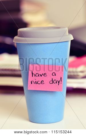 a pink sticky note with the text have a nice day attached to a blue cup of coffee or tea on an office desk