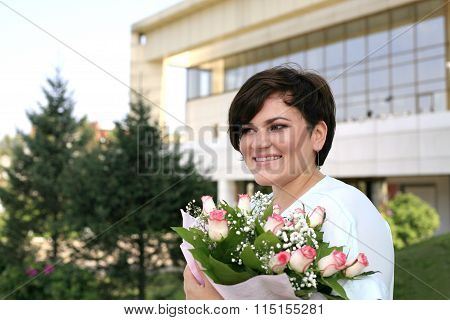 Portrait of a smiling woman Caucasian appearance with a bouquet of roses. on open air. Clear sunny summer day. Short haircut. Beautiful bouquet.
