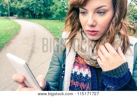 Young Sad Beautiful Woman Texting Message On Mobile Phone In Urban Park - Teenager Model Girl