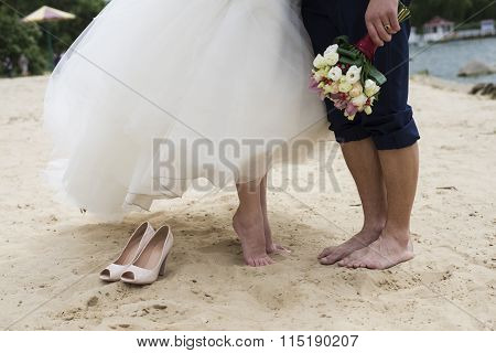 And Bouquet In Hands And Shoes On The Sand