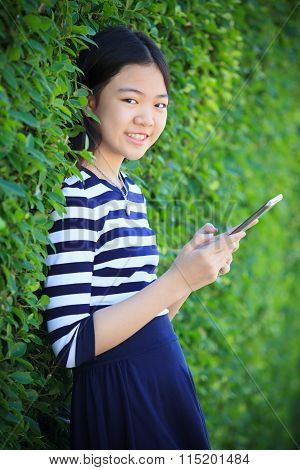 Portrait Of Asian Teen Age ,girl With Computer Tablet In Hand Standing Against Green Garden With Hap