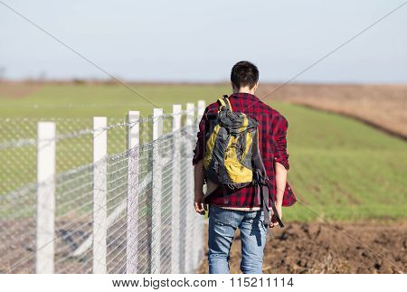 Man With Back Beside Wire Fence
