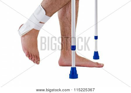 Man Wearing Ankle Brace Walking With Crutches