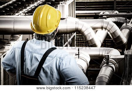 Worker In Protective Uniform And Protective Helmet In Front Of Industrial Pipes - Toned Image, Retro