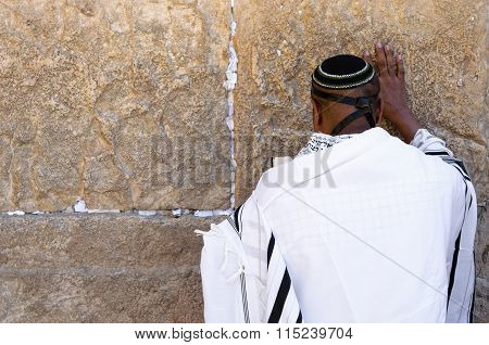 Praying man in front of Western Wall