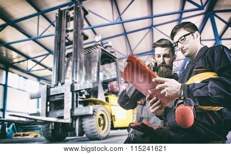 Workers In Protective Uniform In Front Of Forklift