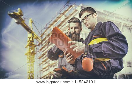 Workers With Protective Uniforms In Front Of Construction Scaffolding And Construction Crane