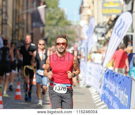 Man Wearing Red Shirt Running In The Triathlon Event
