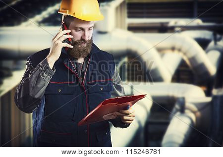 Worker In Protective Uniform With Smart Phone And Clipboard