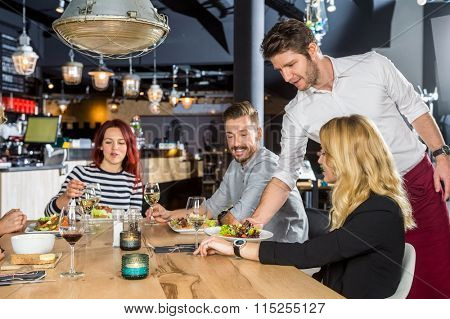 Young waiter serving food to customers at table in cafe