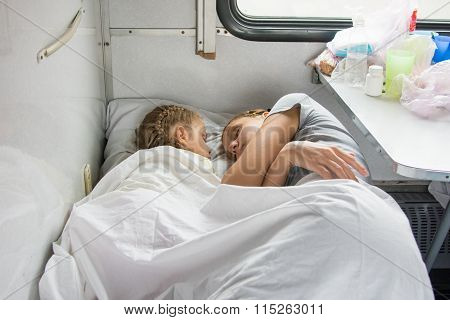 Mom And Daughter Sleeping On The Bottom Shelf In A Train